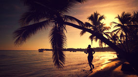 Sea sunrise. Woman running on the tropical island beach Punta Ca. Beautiful sea sunrise. Young woman running on the tropical island beach  Punta Cana, Dominican Stock Photography