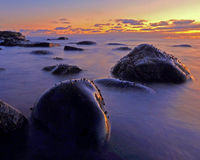 Sea sunset with fog over rocks Stock Images