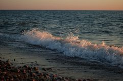 Sea. sunset, beach of pebbles. recreation. Blue sky at sunset.blue water splashing water Stock Images