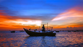 Sea sunset with boat silhouette, man Stock Image