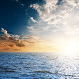 Sea and sunset in cloudy sky. Dark sea and sunset in cloudy sky Stock Images