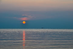 Sea sunset and fishing boat on the horizon Stock Photos