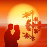 Sea sunset. Island with palm trees and couple. Royalty Free Stock Image