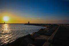 Sea sunset and lighthouse. Path to light house along coastline beach at Den Haag, Netherlad Stock Image