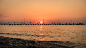 Sea  Sunset at old Jetty with people silhouettes walking and fis Stock Photos