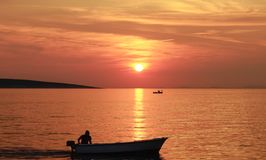 Sea sunset in orange color tone with silhouette man in the small boat royalty free stock photo