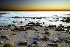 Sea at sunset, sandy and rocky beach Royalty Free Stock Images