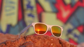 Sea sunset reflected in sunglasses lying on the stone. Sea sunset reflected in white sunglasses lying on the stone with colorful graffity on background stock footage
