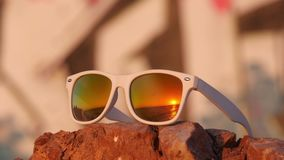 Sea sunset reflected in sunglasses lying on the stone. Sea sunset reflected in white sunglasses lying on the stone with graffity on background stock video footage