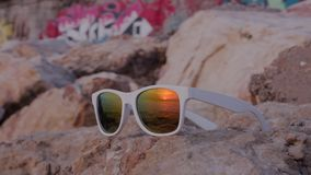 Sea sunset reflected in sunglasses lying on the stone. Sea sunset reflected in white sunglasses lying on the stone with graffity on background 4K Time-lapse stock footage