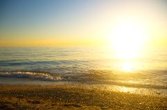Sea sunset. The bright summer sun sets over the sea horizon Royalty Free Stock Image