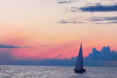 Sea sunset and yacht, autumn weather. Beautiful fall sunset and sailboat in ocean Stock Photos