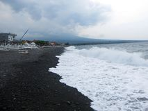 Waves, surf and sea foam hitting the sandy black volcanic sand beach of Bali. In Amed, the sea is quiet, but the waves around the royalty free stock image