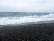 Waves, surf and sea foam hitting the sandy black volcanic sand beach of Bali. In Amed, the sea is quiet, but the waves around the stock images