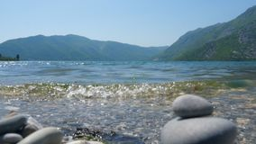 Sea surf on a background of mountains. A close up shot of a surf on a pebble beach against the backdrop of mountains and a blue sky stock video