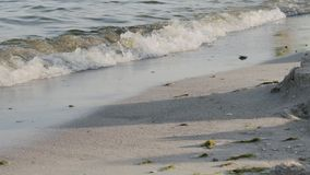 Sea surf, close-up of man's feet running out of the sea to shore.