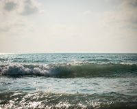 Sea with surf and cloudy sky Stock Image