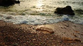 Sea surf at the coast. Sunny water with white foam splashing to the pebble beach, natural summer vacation relaxing concept stock footage