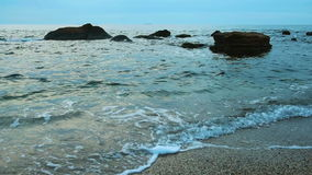 Sea surf at the coast. Water with white foam splashing to the pebble beach, natural summer vacation relaxing concept stock video