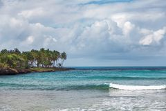 Sea surf in the Dominican Republic. Sea, shore with palm trees and sky with storm clouds. Sea surf in Samana, Dominican Republic. Sea, shore with palm trees and Stock Photos
