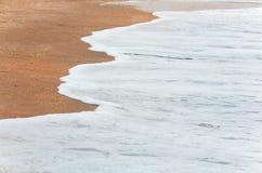 Sea surf foam on coastline sand Stock Image