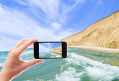Sea surf. Hand with smartphone on the background of the sea Stock Images