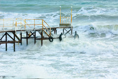Sea surf pier. Wooden pier at the sea shore during winter Royalty Free Stock Image