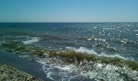 Sea surf on a sunny day. View of the sea from the dam. royalty free stock photos