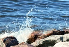 Sea surf and wave splashing about coastal granite rocks.  royalty free stock photos