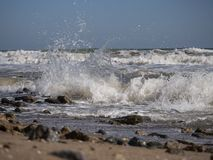 Waves splash and roll on a sandy beach stock photos