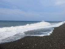 Sea surf and waves crashing onto the beach stock photography