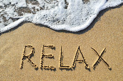 Sea surf and the word relax on the sand.  royalty free stock photo