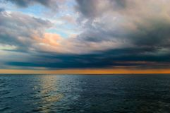 Orange sunset on the sea. The sea surface of the ocean at sunset orange, clouds and clouds in the evening storm Stock Image