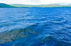 Sea surface with slight rippling water with a mountain landscape in the background.  royalty free stock photography