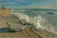 Sea surge. The force of the water moves a big rock stock photography