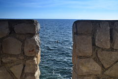 Sea and swimmers through a stone wall Stock Photo