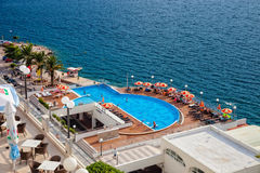 Sea with swimming pool. People resting at the pool area at popular hotel Sunce at the Adriatic sea coastline on July 23, 2014 in Neum, Bosnia and Herzegovina Stock Images