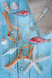 Sea On The Table. Concept of sea on the table: raw lobsters, scorpionfish and seashells on blue wooden background Stock Photos