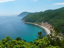 Sea and Taiga. The view from above on small bay. Azure and summer. Russian Far East, Primorye, state nature reserve Lazovsky, Japanese sea, Uglovaya bay Royalty Free Stock Image