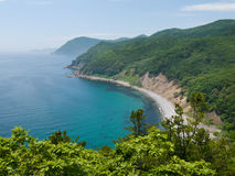 Sea and Taiga 7. The view from above on small bay. Azure and summer. Russian Far East, Primorye, state nature reserve Lazovsky, Japanese sea, Uglovaya bay Stock Images