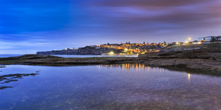 Sea Tamarama Town rise pan. Colourful panoramic view towards tamarama residential suburb and beach at sunrise with lights reflecting in still sold water puddle Stock Image