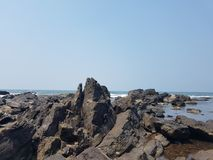 Rocky beach shore. From the sea there are sharp, long and short stones Stock Photos