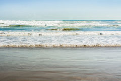 Sea tidal waves with white foam on a sunny sandy beach in resort Royalty Free Stock Images