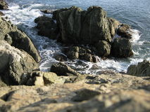 Sea tide. Waves and coast rocks Royalty Free Stock Image