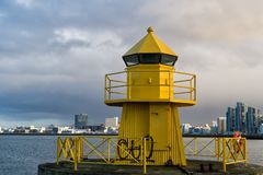 Sea transportation and navigation. Lighthouse on sea pier in reykjavik iceland. Lighthouse yellow bright tower at sea. Shore. Seascape and skyline with bright royalty free stock photos