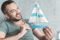 Joyful guy with stubble is playing with small yacht Stock Photos