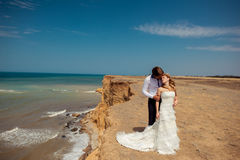 Sea travel, happy couple hugging on  side near hot summer water of ocean. Honeymoon picture with copy space Royalty Free Stock Photo