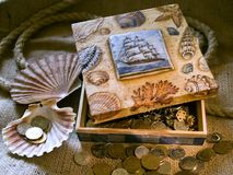 Sea treasure. Painted box filled with coins Royalty Free Stock Photo