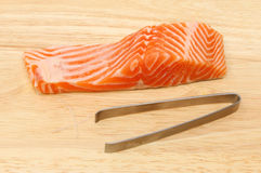 Sea trout fillet and tweezer Royalty Free Stock Photography