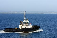 Sea tugboat under power in harbour. Stock Photos